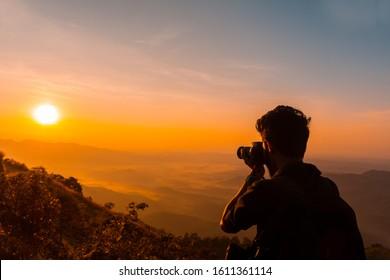 Travel Photographer taking photos of mountains scenery during the sunrise,beautiful Nature landscape scenery shot from Palakkayam Thattu Kannur, Kerala Travel and Tourism Concept Image, indian tourism
