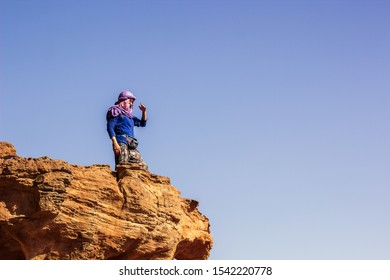 travel photography of touristic woman in hijab stay of edge of cliff desert rock on empty blue sky background space for your text