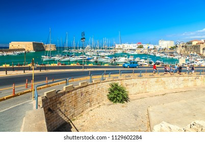 Travel photography: tourists down a winding road Fishing boats. Port of Heraklion, Crete, Greece
