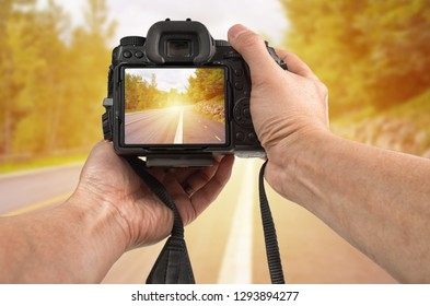 Travel phototography concept. Man's hands holding a camera taking picture of a street