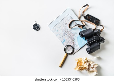 Travel plan background. Map, binoculars, compass, magnifier and crumpled paper on white paper background. Flat lay.