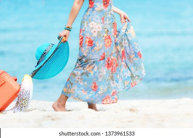 Travel Plan. Hand women traveler holding orange luggage walking on the beach. Traveler and Tourism planning trips summer vacations with Traveler's accessories summertime. Summer Concept