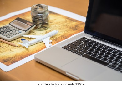 Travel and planing concept. Airplane toy model with laptop computer, calculator full of coins in bottle, pencil and world map.