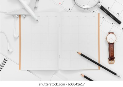 Travel Planning. Airplane, pencil, notebook, earphone, magnifying glass, watch and travel itinerary, on white background with blank space. Preparation for Traveling and Flat lay Concept.