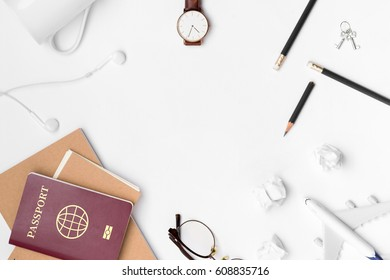 Travel Planning. Airplane, pencil, watch, eyeglasses, paper note, key, notebook, earphone, and passport with blank space on white background. Preparation for Traveling and Flat lay Concept.