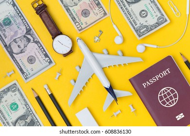 Travel Planning. Airplane, pencil, watch, money, paper note, paper cilp, earphone, and passport with blank space. Preparation for Traveling and Flat lay Concept.