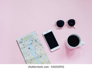 Travel planning concept : map, smartphone, sunglasses and hot coffee cup on pink background, top view with minimal style
