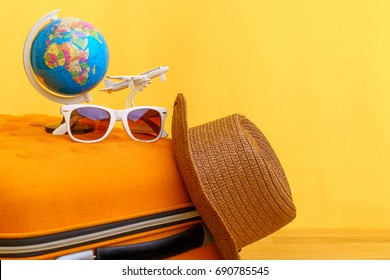 Travel planning for holiday vacation trip concept with airplane and globe on wooden table and yellow background