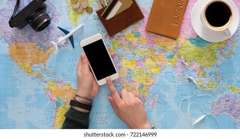 Travel planning online concept. Searching or booking tickets online, preparation for summer vacation, tourist stuff and blank smartphone on map background, top view