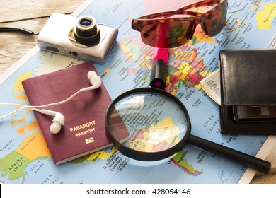 Travel planning over world map. Passport and magnifying glass