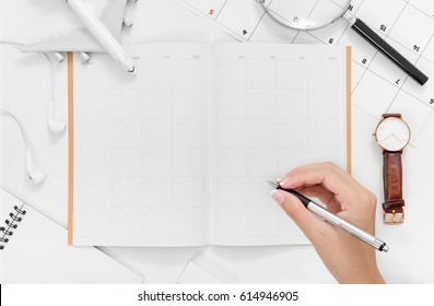 Travel Planning. Woman hands writing her travel plan on travel itinerary. Airplane, pen, watch, notebook, earphone, magnifying glass and time schedule. Preparation for Traveling and Flat lay Concept.