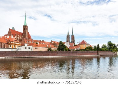 travel to Poland - old Collegiate Church of the Holy Cross and St Bartholomew and towers of Cathedral of St John the Baptist in Ostrow Tumski district in Wroclaw city from Oder River