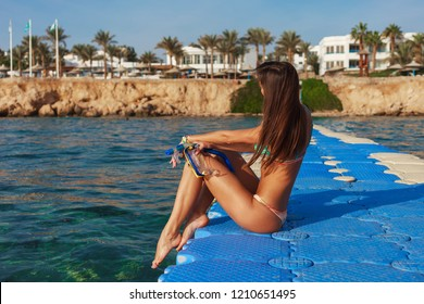 Travel portrait of smiling female outdoors on the pier on Red Sea, Egypt. Happy woman in bikini with snorkeling equipment. Luxury sport tourism concept in tropical country.