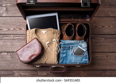 Travel preparations concept with open suitcase and woman's casual clothes