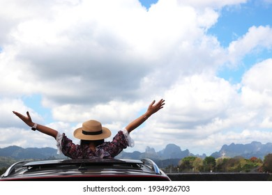 travel, Rear view of young happy people, road trip and people concept - happy young woman wearing hat and raising their arms up in convertible car
