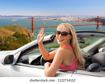 travel, road trip and people concept - happy young woman in convertible car waving hand over golden gate bridge in san francisco bay background