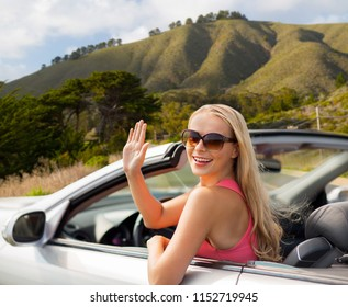 travel, road trip and people concept - happy young woman in convertible car waving hand over big sur hills background in california