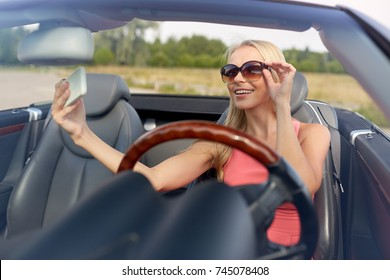 travel, road trip and people concept - happy young woman in convertible car taking selfie by smartphone