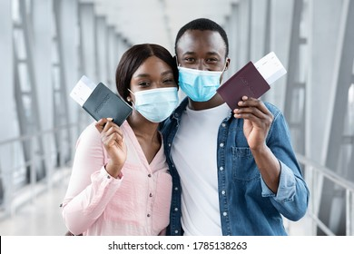 Travel Safe During Coronavirus Pandemic. Black couple in protective medical masks posing with passports and tickets at airport, closeup