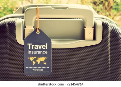 Travel safety and travel insurance concept : Travel insurance tag is tied on a luggage or baggage handle. Travel insurance is intended to cover lost luggage, trip cancellation, accident, losses, etc