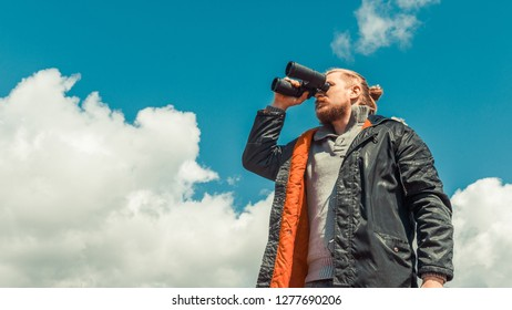 Travel Search Scout Concept. Strong Traveler Man Looking Through Binoculars In The Distance Overview Sky. Low Angle Point Shoot