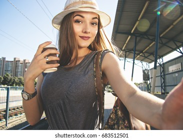 Travel selfie. Beautiful and young woman in dress and hat keeping camera in hand and smiling while taking selfie with coffee on train stop during city travel.