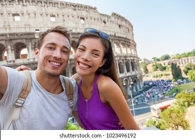 Travel selfie couple taking photo with phone at colosseum famous landmark in Rome city. Europe Italy summer vacation young people smiling. Backpacking road trip.