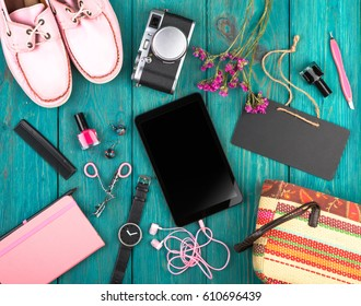 Travel or shopping concept - accessories, shoes, tablet pc, camera, bag, note pad, watch, headphones, blackboard and essentials on blue wooden desk