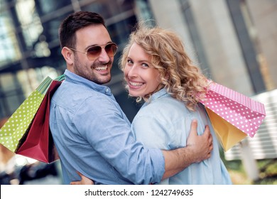 Travel and shopping concept - couple of happy tourists walking with shopping bags.