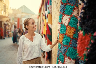 Travel and shopping. Young traveling woman with choose presents in souvenir shop in Morocco.