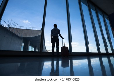 travel, silhouette of passenger in airport, man with luggage waiting for the flight in terminal gate
