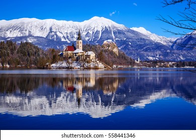 Travel Slovenia, Europe. Winter landscape Bled Lake. Bled Lake one of most amazing tourist attractions. View on Island with Catholic Church in Bled Lake with Castle and snowy Alps in Background.
