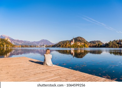 Travel Slovenia, Europe. Woman sitting on a wooden pier and looking on Bled Lake with Island, Castle and Alps Mountain on background.