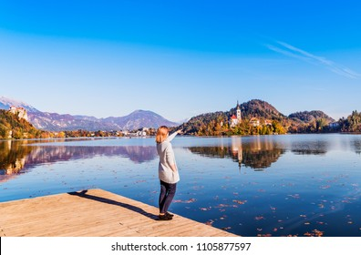 Travel Slovenia, Europe. Young woman looking at Bled Lake and Alps Mountain. Bled Lake is amazing tourist attractions.