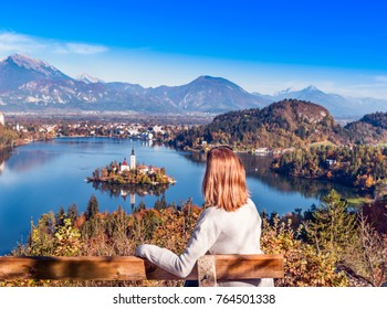 Travel Slovenia, Europe. Young woman looking at Bled Lake and Alps Mountain. Bled Lake is amazing touristic attractions.
