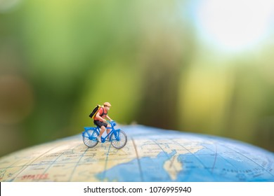 Travel and Sport Concept. Miniature figure of man ride bicycle on world balloon