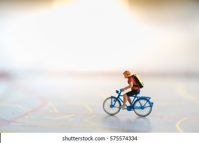 Travel and Sport Concept. Miniature people figure of man ride bicycle on map