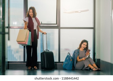 Travel, Study abroad concept - Two happy Asian girls using smartphone checking flight or online check-in, listening to music and holding shopping bags, passport, carrying suitcase at airport.