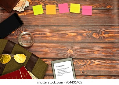 Travel stuff on wooden surface - military style backpack, tablet with to do list, wallet with euro notes, glass with water, passports, map. Travel preparations concept, holidaymakers workspace.