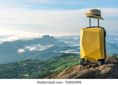 Travel suitcase with hat on the nature of beautiful mountain landscape and mist, relaxing time, holidays, weekend and traveling concept.