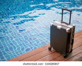 Travel suitcase is located by the pool.