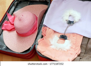 travel suitcase, sun hat, underwear and handcuffs for adult games on wooden background, flat lay, sex tourism business concept. bdsm