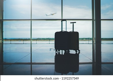 Travel suitcases in empty airport terminal waiting area, vacation concept or business travel, two suitcases in departure lounge, airport hall interior with large windows, airplane taking off
