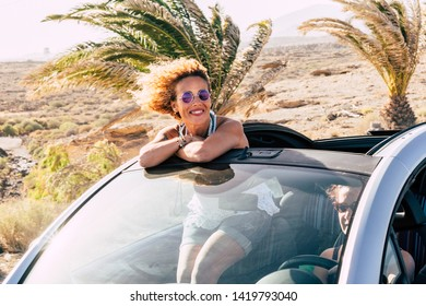 Travel summer holiday vacation concept with young caucasian cheerful people women couple traveling with convertible car together in friendship - tropical background and freedom lifestyle