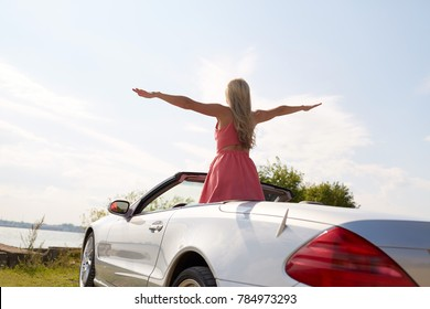 travel, summer holidays, road trip and people concept - happy young woman in convertible car enjoying sun at seaside