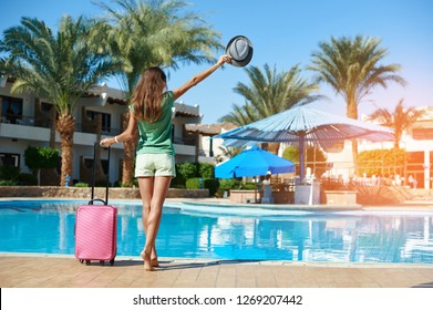 Travel, summer holidays and vacation concept - Beautiful woman walking near hotel pool area with pink suitcase