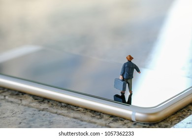 Travel and technology concept. Businessman miniature figure with suitcase standing and walking on smart phone.