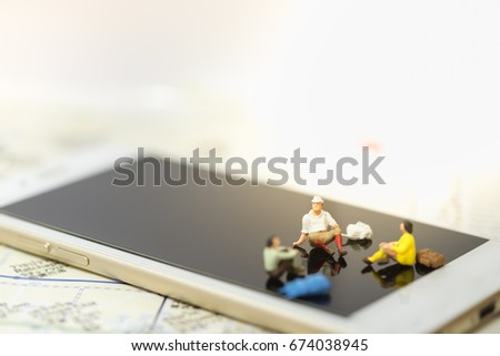 Travel and Technology Concept. Group of traveler miniature people figure with backpack sitting, rest and talking on smart phone screen on map.