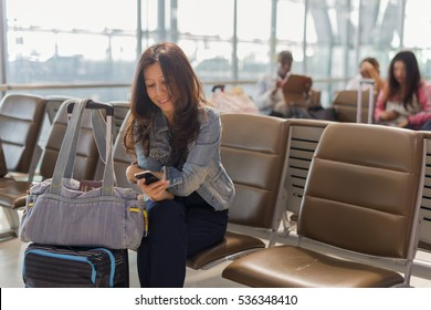 Travel and technology concept.  Smile Asian woman at international airport using smartphone and passport on her's luggage while waiting for her flight and background blur passenger. (lens blur effect)