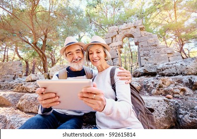 Travel and technology. Senior traveling family couple using tablet computer at ancient sightseeing.
